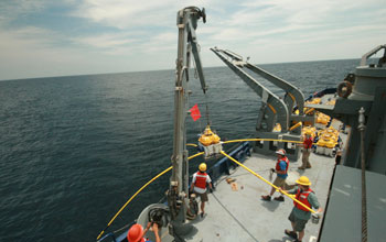 Photo of a crew on a ship using a crane to deploy a receiver in the ocean