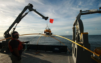 Researcher on a ship pulls a receiver from the ocean using a crane