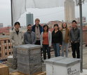team of researchers with bee boxes on roof of texas building
