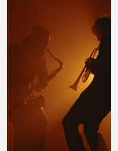 Photo of men playing a saxaphone and a trumpet.