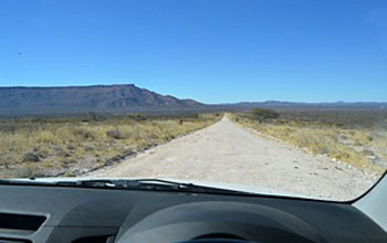 View through fron window of vehicle showing unpaved gravel road in Namibia.
