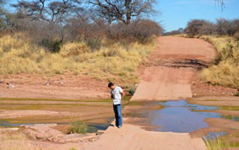 Photo of geologist Kyle Nichols standing next to wet river crossing in Namiba.