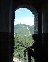 Photo of Meghan Schulz looking out from a watchtower on the Great Wall at Mutianyu.