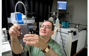 Photo of Professor Wachs examining an environmental reaction cell into which he places catalysts.