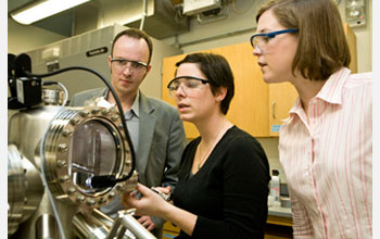 Photo of Charles Sykes and two graduate students using a scanning tunneling microscope.