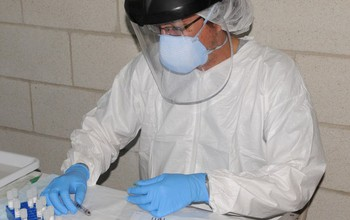 resarcher in lab gear doing tests
