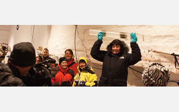 Photo of a woman in a snowsuit standing in a crowd inside a lab building holding a long ice core.