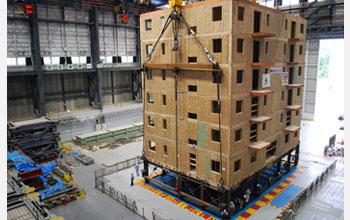 Photo of a six-story condominium building being transported for a full-scale earthquake test.