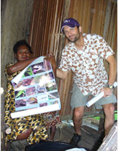 Photo of Chris Austin giving an educational conservation poster to the headmaster's wife