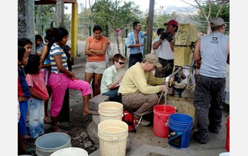 Photo of John Gierke measuring the water level, with people and buckets around him