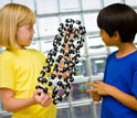 Photo of children talking about a model of a carbon nanotube.