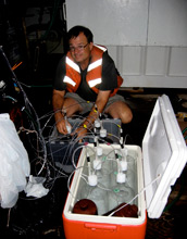 Photo of David Hutchins preparing an experiment with marine microbes.