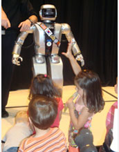 Photo of children reaching out for Jaemi Hubo, an NSF-funded international robotics collaborative.