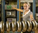 Photo of Laura Saxton testing a multi-cell superconducting radio frequency cavity prototype.