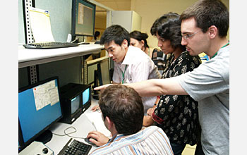 Photo shows Exotic Beam Summer School students viewing progress of their experiments.