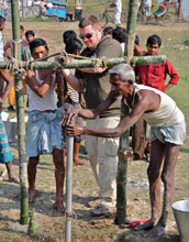 Image of graduate student Thomas Hartzog assisting in the drilling of a tube well in Bangladesh.