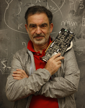 Tomaso Poggio stands in front of a blackboard holding a computer part.