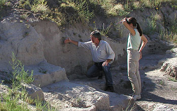 Two researchers examine at fossil site.