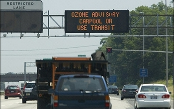 cars on highway and display showing ozone advisory