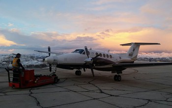 The King Air moves into a hangar; snow clouds are in the background.