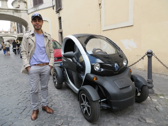 Ricardo Daziano stands next to a full-electric vehicle in Rome, Italy.
