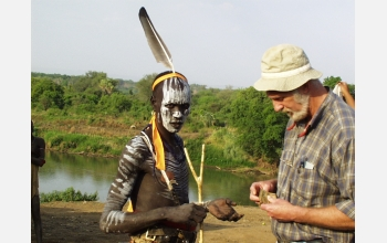 Frank Brown and a Mursi warrior examine a sample of colored rock.