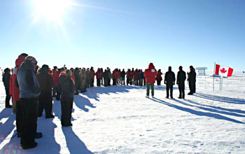 A memorial ceremony at South pole showing people gathered on the ice and the Canadian flag.