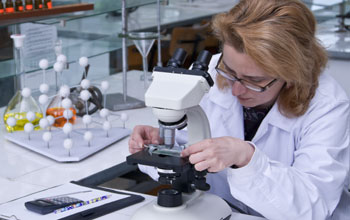 Photo of a scientist working with a microscope in a lab