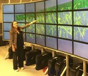 woman standing next to wall of screens.