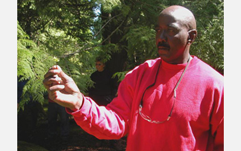 Photo of a Cedar Creek inmate and researcher in the Moss-in-Prisons project holding moss.