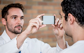Man holding a smartphone in front of another man