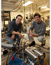 Photo of researchers kneeling behind a dilution refrigerator equipped for microwave measurements.
