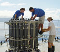 Photo of scientists preparing a rosette that will bring back seawater samples.
