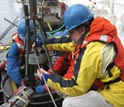 Photo of WHOI scientist Bruce Keafer, right, preparing a corer to collect seafloor sediment samples.