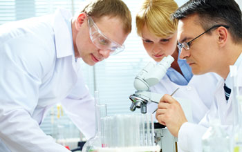 Photo of three researchers in lab coats and a microscope and test tubes on a table.