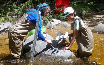 A LoVoTECS coordinator and volunteer scientists mount/calibrate aquatic sensors in New Hampshire.