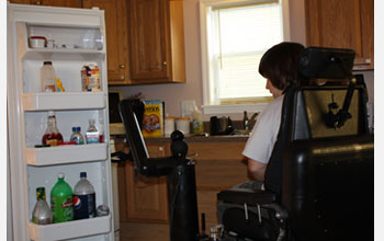 Photo of person with disabilities piloting a robotic mobility and manipulation system in kitchen.