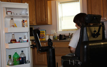 Photo of a disabled person piloting a robotic mobility and manipulation system to open frig door.
