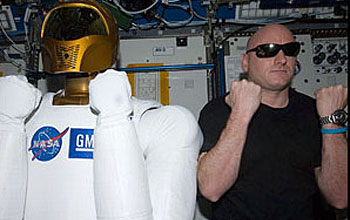 Photo of dexterous humanoid helper Robonaut 2 with Scott Kelly in International Space Station lab.