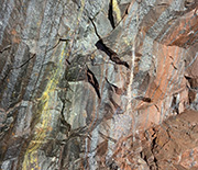 A close-up shows the rocks that make up a wall of the underground mine.