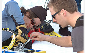 "Photo shows Gretchen Hofmann and Tom Crombia carrying out a ""field repair"" on the rover."