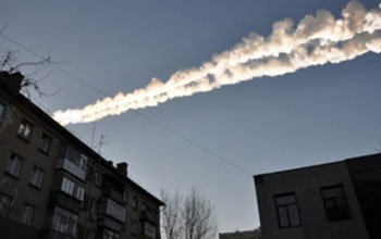 Sky showing a meteor as it streaked by buildings in Russia.