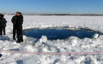 People standing next to hole in the ice at Russia's Lake Chebarkul, said to be caused by the meteor.