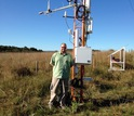 Scientist standing next to cosmic-ray soil moisture sensor