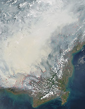 thick gray smoke hovers over the Southeast Asian island of Borneo