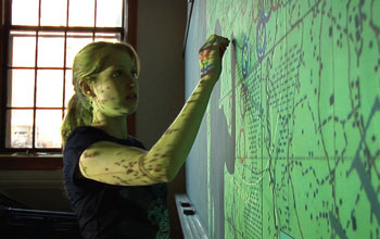 Photo of a young woman writing on a virtual green image projected onto a wall.