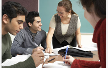 Photo of graduate students working at a classroom table.