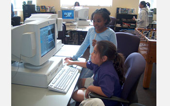 Photo of middle school children working at a computer.