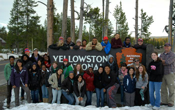 Photo of people gathered around sign Yellowstone National Park with the National Park Service logo.