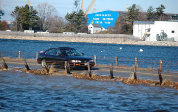 Photo of a car crossing a nearly submerged causeway along the New Hampshire coast.